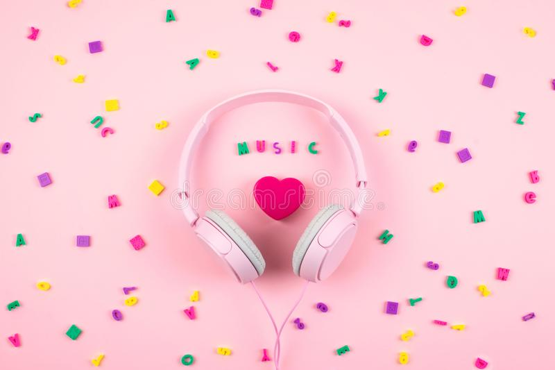 Pink headphones and heart with word MUSIC and multicolored letter symbols on pink background. Minimal Music concept. Top view. Flat lay royalty free stock image