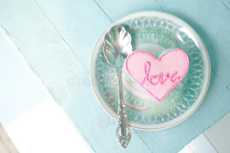 A pink heart cake with love message on the cake. Top view. stock photos