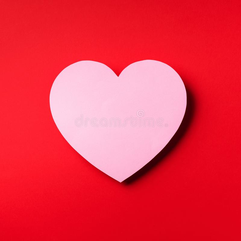 Pink heart cutted from paper over red background with copy space. Top view. Valentine's Day. Love, date, romantic concept. Square. Crop stock photography