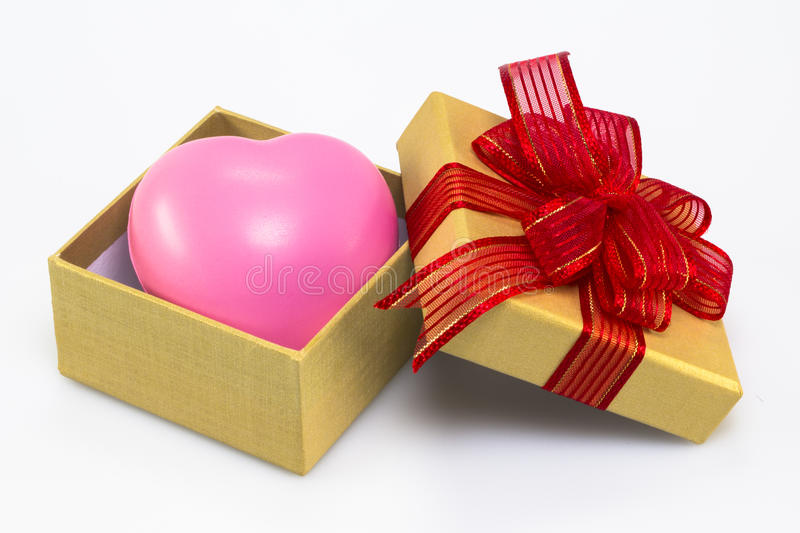 PINK HEART IN GOLDEN GIFT BOX. On white background royalty free stock images