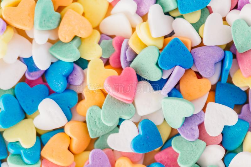 Pink heart in heap of colorful hearts candies. Valentine day holiday. royalty free stock photography