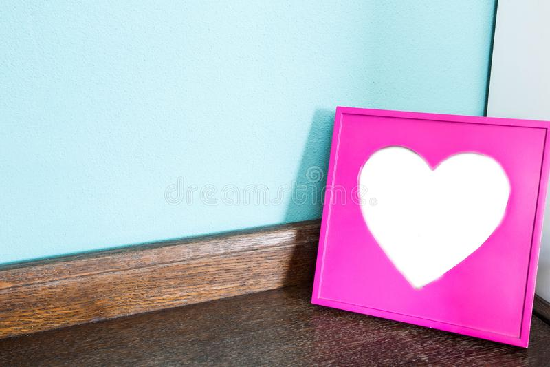 Pink heart picture frame on wood table with blue wall background, space for text stock images