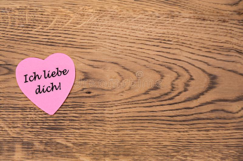 Pink heart post-it with the text `Ich liebe dich` on a wooden background. Translation: `I love you`. Pink heart post-it with the black text `Ich liebe dich` vector illustration