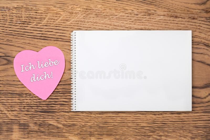 Pink heart post-it with the text `Ich liebe dich` and a notebook on a wooden background. Translation: `I love you`. Pink heart post-it with the white text `Ich royalty free stock image