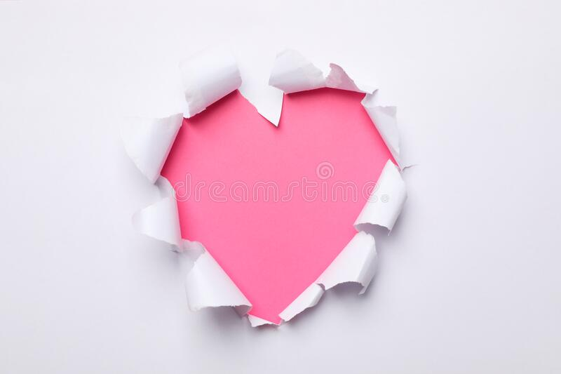 Pink heart shape hole through paper stock images