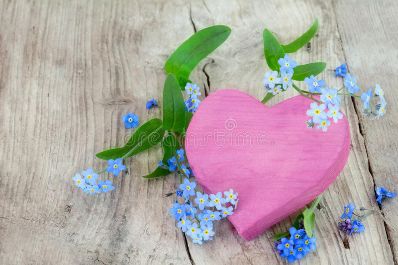 pink heart shape made of wood with forget-me-not flowers on a wooden background stock photo