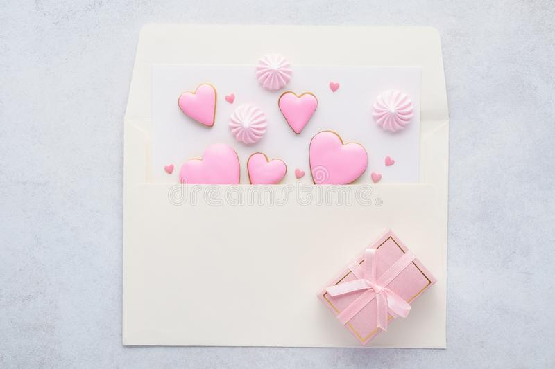 Pink heart shaped cookies in an envelope and a gift box. stock photography