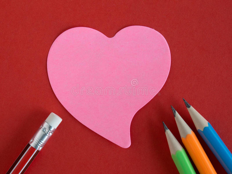 Pink heart-shaped memorandum on red paper with colorful pencils. And eraser (meaning of love, remember and forgiveness royalty free stock image