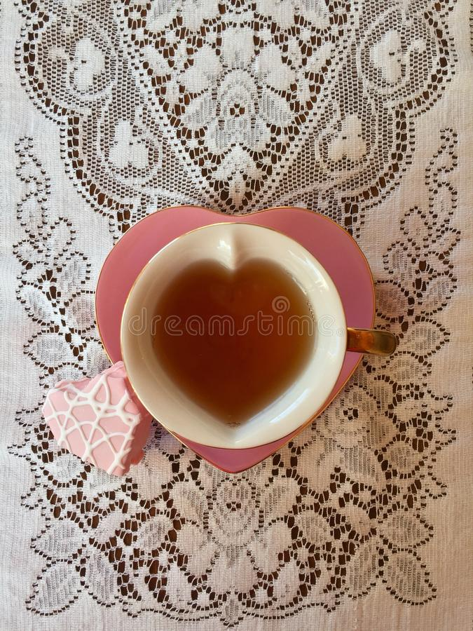 Pink heart shaped teacup with heart shaped frosted cake. This is a pink heart shaped teacup filled with tea and heart shaped saucer. It is sitting on ivory royalty free stock photography