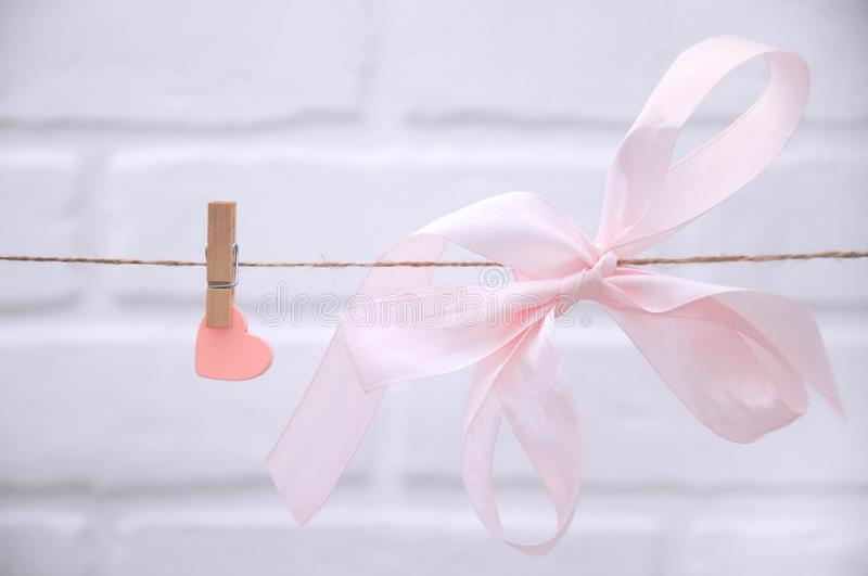 Pink heart with silk bow hanging from a rope with clothespins on a white background. royalty free stock photos