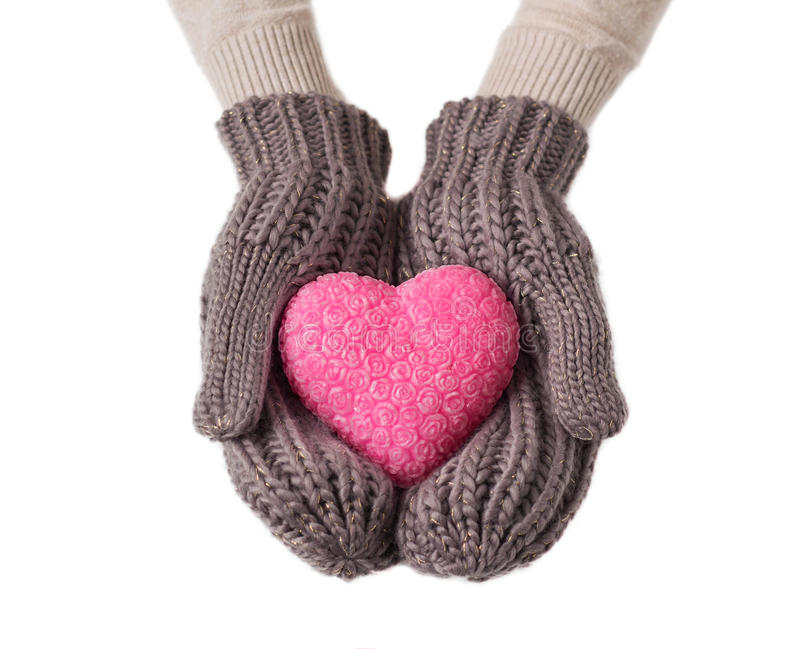 Pink heart in wool gloves. Pink heart in warm wool gloves isolated on white background stock image