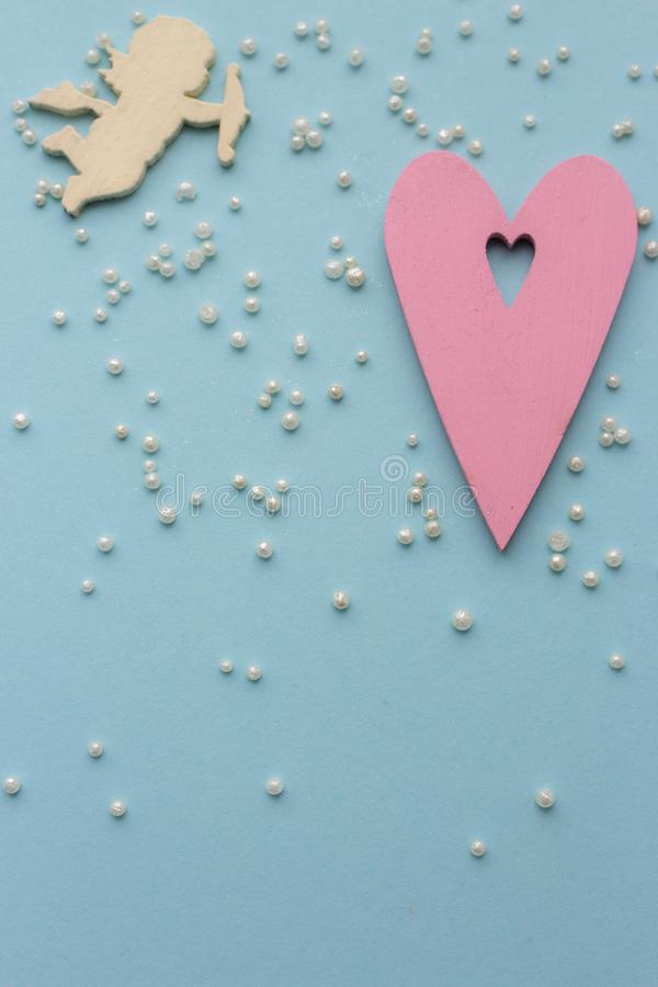 Pink heart and yellow love angel on azure background with white pearl beads. Wedding concept. royalty free stock photos