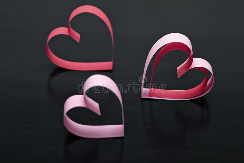 Pink hearts made from paper on a dark wooden background. royalty free stock images