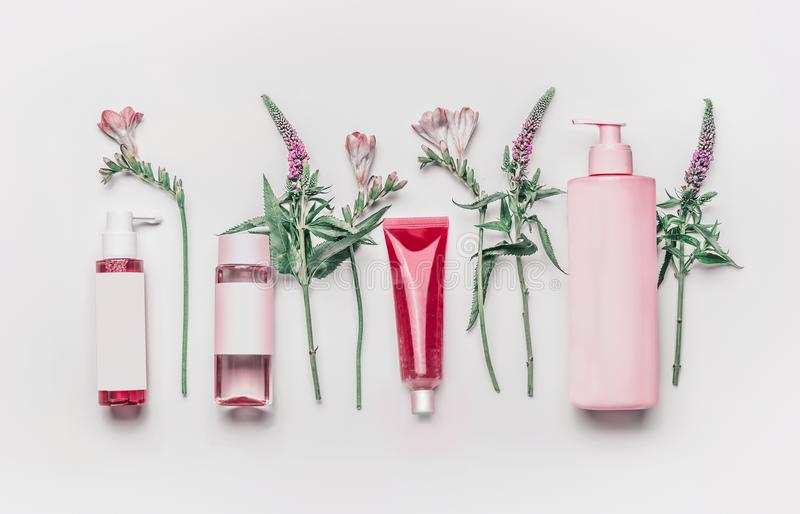 Pink herbal natural facial cosmetic products set with herbs and flowers on white background stock photos