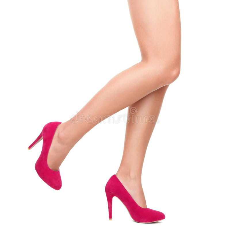 Pink high heels and legs royalty free stock image