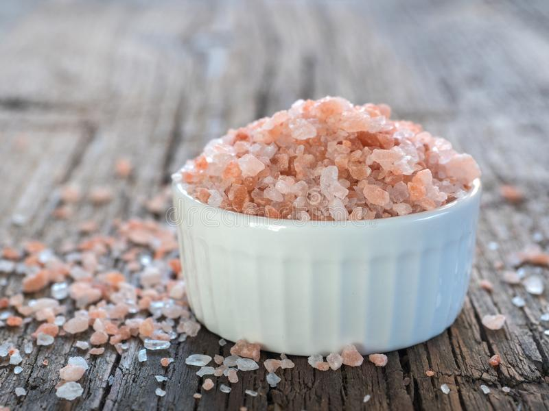 Pink Himalayan salt in white salt shaker on wooden background. Healthy spice closeup stock photo