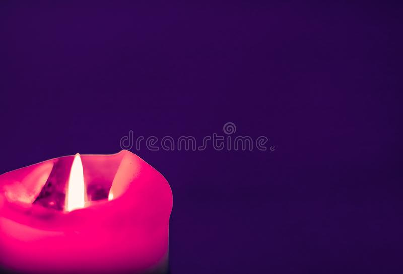 Pink holiday candle on purple background, luxury branding design and decoration for Christmas, New Years Eve and Valentines Day. Happy holidays, greeting card royalty free stock photos