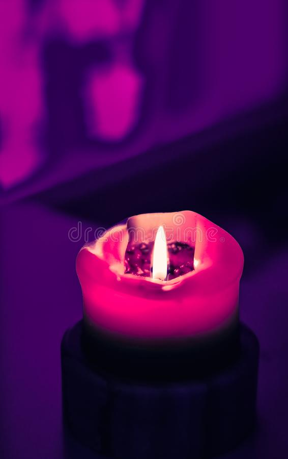 Pink holiday candle on purple background, luxury branding design and decoration for Christmas, New Years Eve and Valentines Day. Happy holidays, greeting card stock images