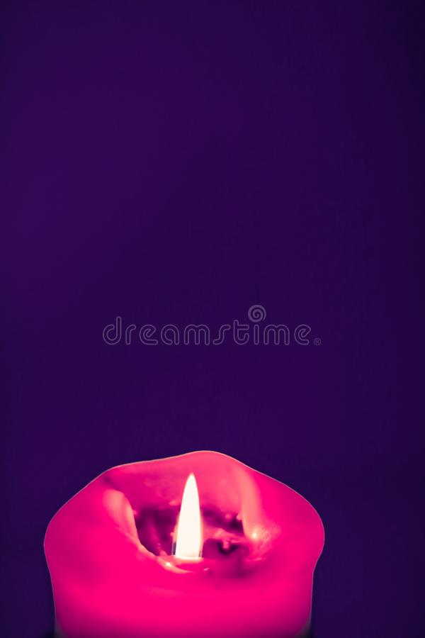 Pink holiday candle on purple background, luxury branding design and decoration for Christmas, New Years Eve and Valentines Day. Happy holidays, greeting card stock photo