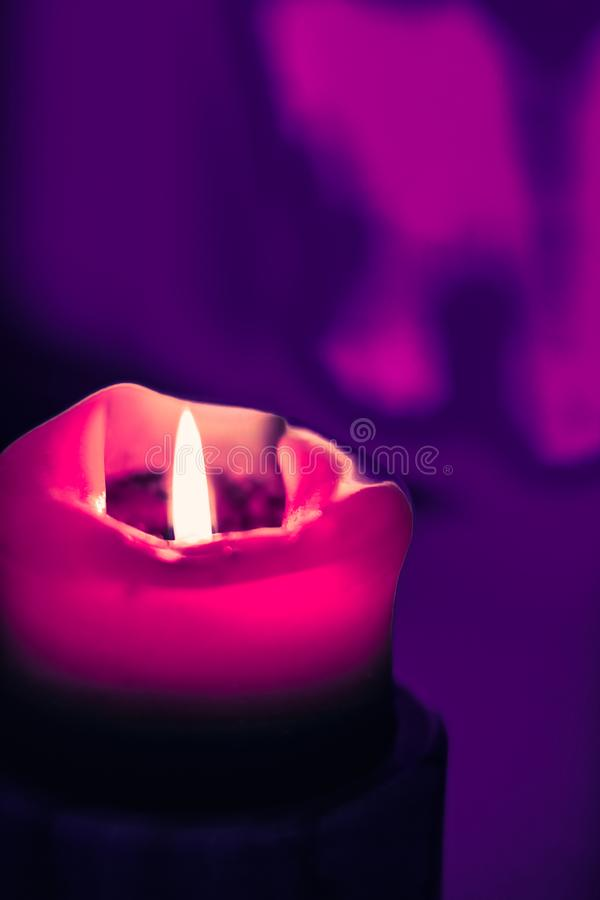 Pink holiday candle on purple background, luxury branding design and decoration for Christmas, New Years Eve and Valentines Day. Happy holidays, greeting card stock image