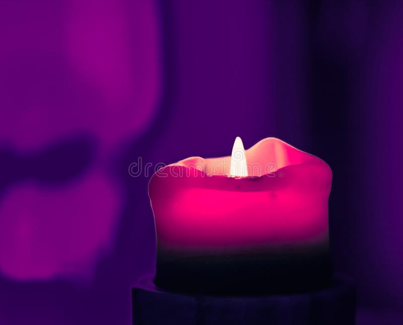 Pink holiday candle on purple background, luxury branding design and decoration for Christmas, New Years Eve and Valentines Day. Happy holidays, greeting card stock photos