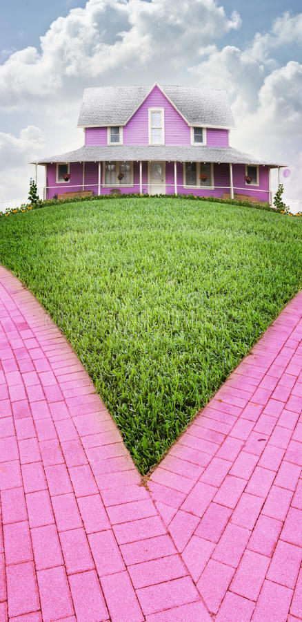 Pink house. A pink pretty house on a hill with a green lawn and pink brick drive. Concept for an ideal home in a perfect neighborhood