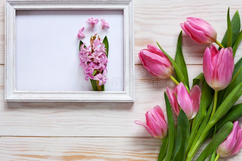 Pink Hyacinth in white wooden frame And Bouquet of pink tulips. Top view, close-up, flat lay on white wooden background royalty free stock photo