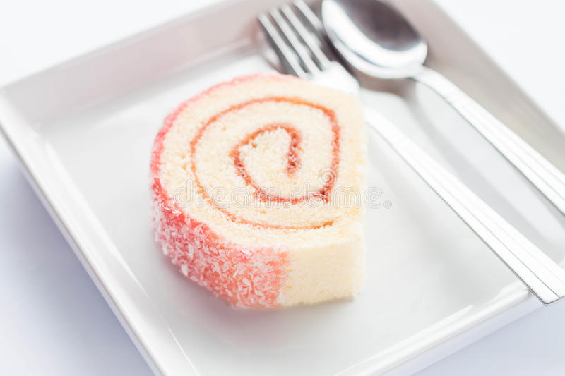 Pink jam roll cake with spoon and fork. Stock photo stock images
