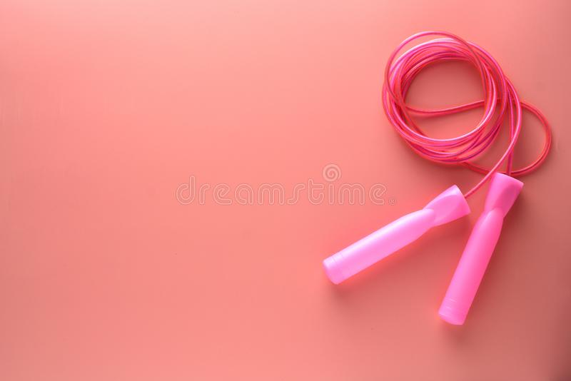 Pink jumping rope or skipping rope isolated on pink background. Sports, fitness, cardio, healthy workout concept stock images