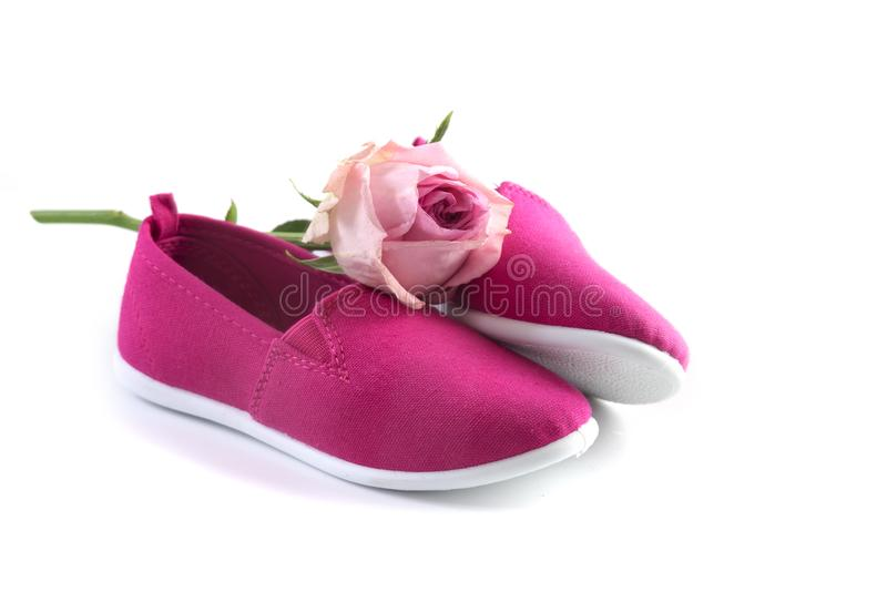 pink kid shoes and a rose isolated on a white background, concept International Day of the Girl Child on 11 October, copy space stock image