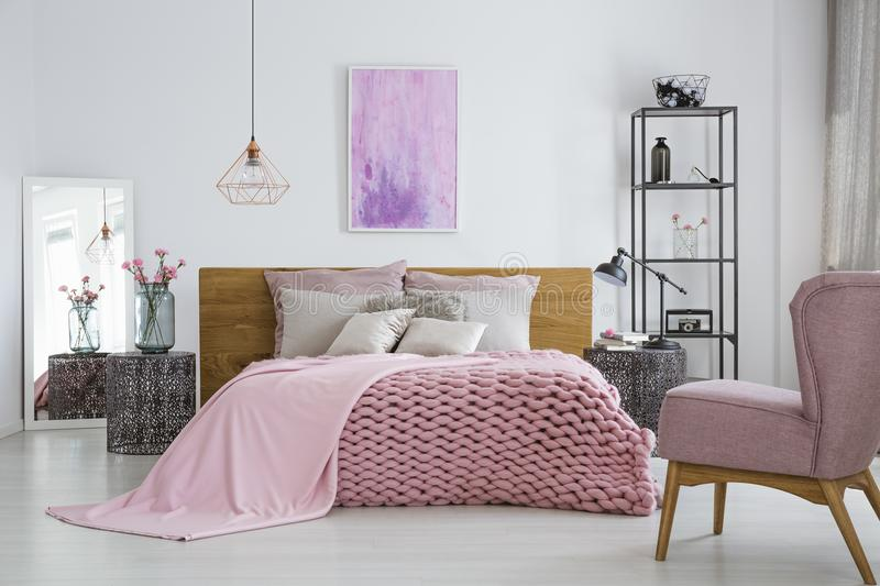 Knit blanket in feminine bedroom. Pink knit blanket covering double bed with decorative pillows standing in the middle of feminine bedroom interior royalty free stock photo