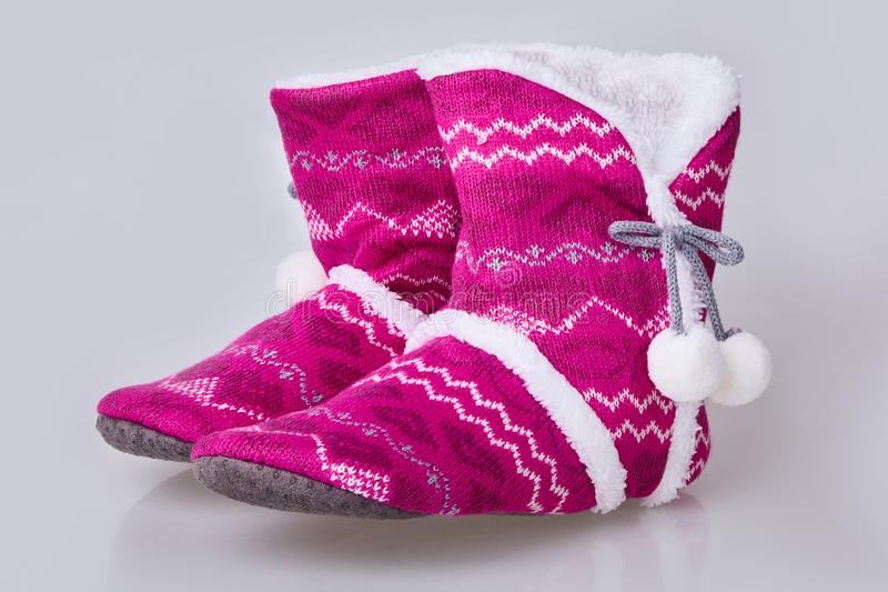 Pink knitted slippers on a white background. Soft warm comfortable home slippers royalty free stock photos