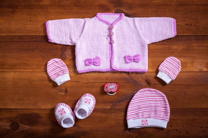 Pink knitted sweater cotton mittens socks cap and dummy on brown wooden background, baby clothes set on table, child newborn stock photography
