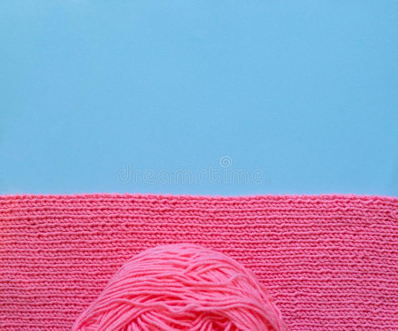 Pink knitting and yarn ball, blue background royalty free stock photo