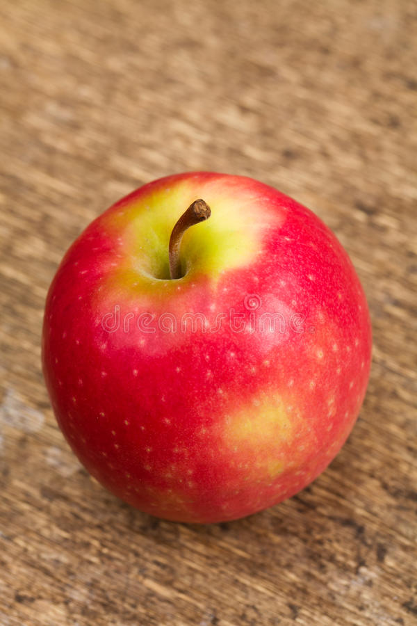 Pink Lady apple. Single Pink Lady apple on wooden background stock images