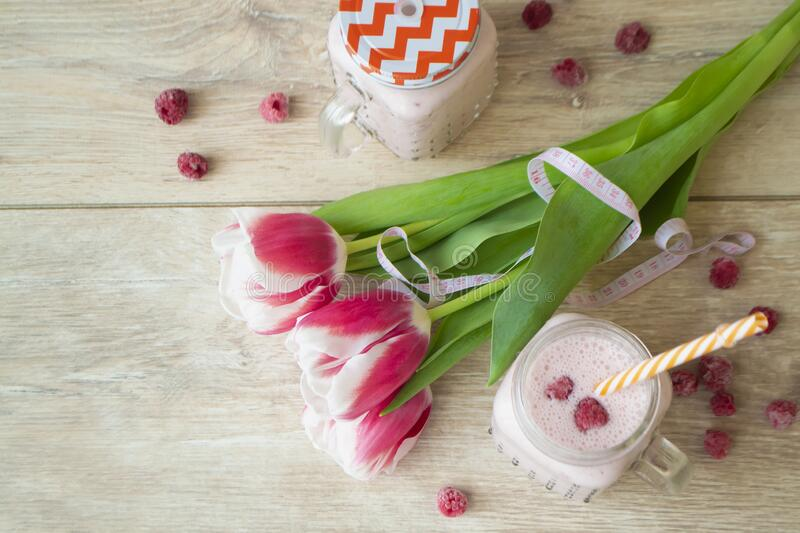 Pink latte healthy beverage trendy beetroot latte and raspberry smoothie, with tulips flowers. Top view image royalty free stock photo