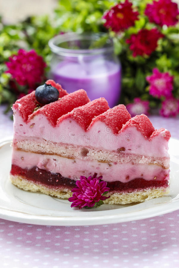 Pink layer cake decorated with fresh fruits. On wooden table. Selective focus royalty free stock images