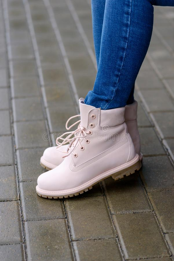 Pink leather boots on woman`s legs stock photo