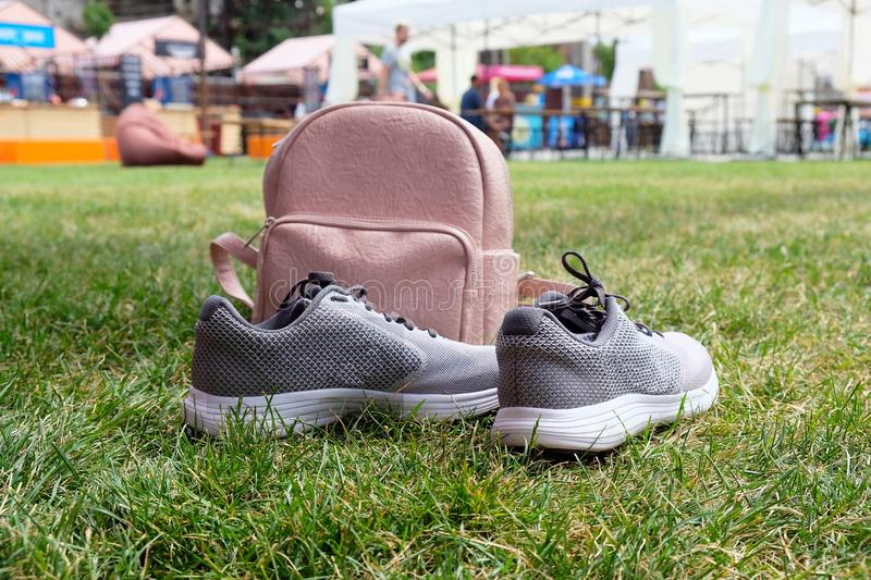 Pink leather female backpack and gray sneakers stock images