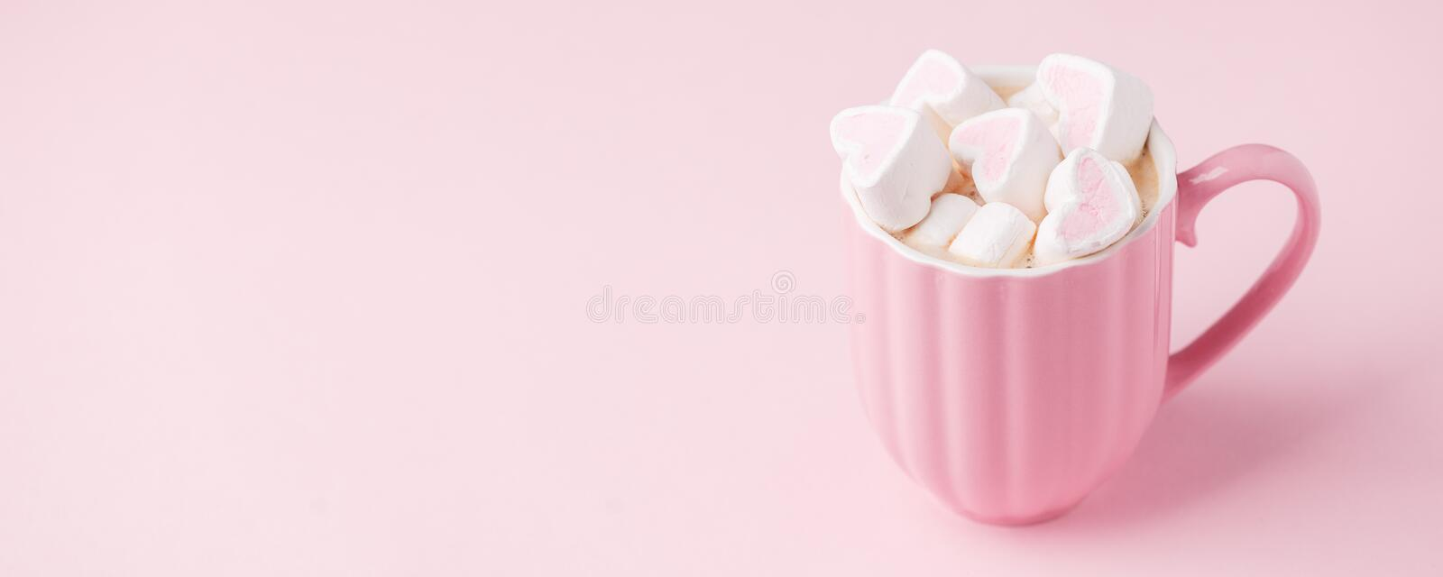 Pink light pastel background. Cup of dark coffee, hearts shaped marshmallow. Valentine`s wedding day concept. Romantic girly royalty free stock images
