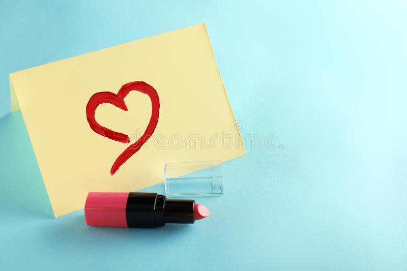 Pink lipstick with drawn heart on paper stock photo