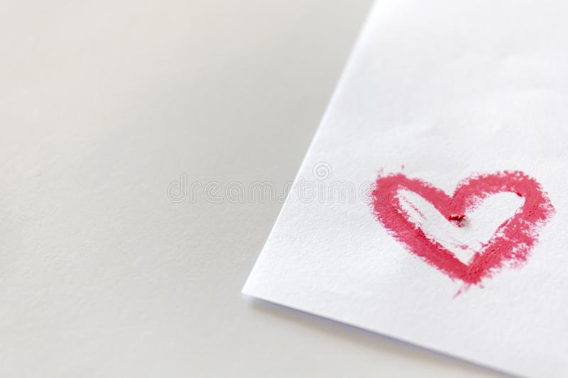 Pink lipstick smeared in heart shape on white paper stock photography