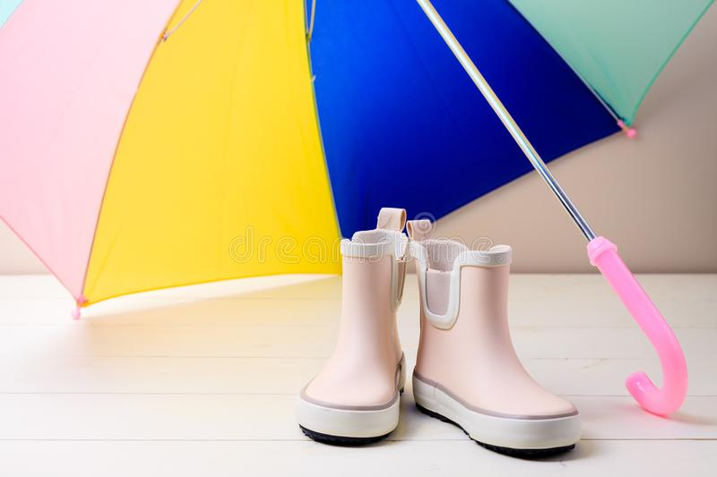 Pink little children rubber boots stand under colorful umbrella. royalty free stock images