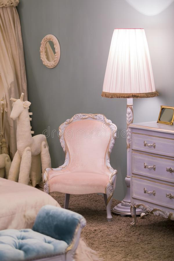 Pink little princess room with a floor lamp by a children`s toy horse and a beautiful chest of drawers, frames on the walls. Luxu royalty free stock photography