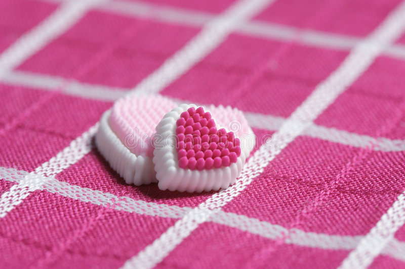 Pink Love. Pink candy hearts on pink plaid royalty free stock image