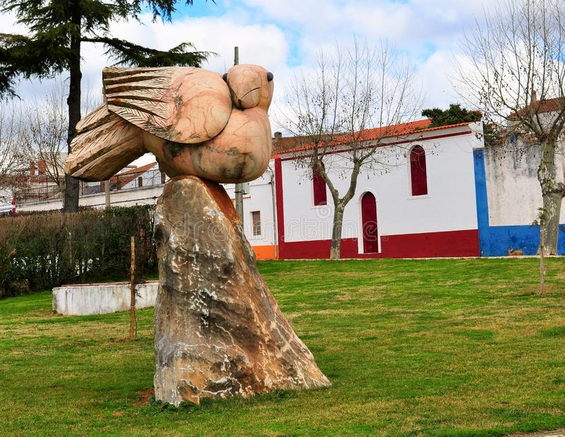 Pink marble statue of a bird in a garden. Photo of a pink marble statue of a bird in a garden - Vila Viçosa, Alentejo, Portugal - February 2017 stock photography