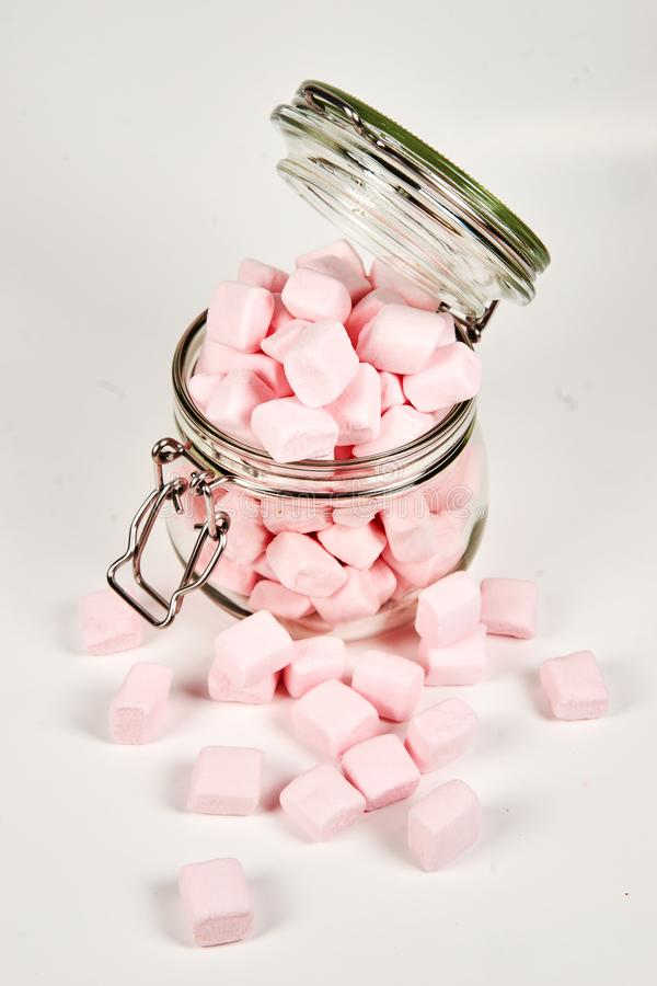 Pink marshmallows in the glass jar, on white background stock photography