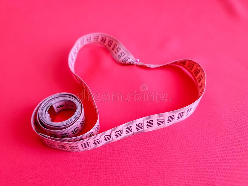 Pink measure tape with black numbers on fabric background. Close up view of the measuring tape. Themes: diet, handmade, home decor stock photography