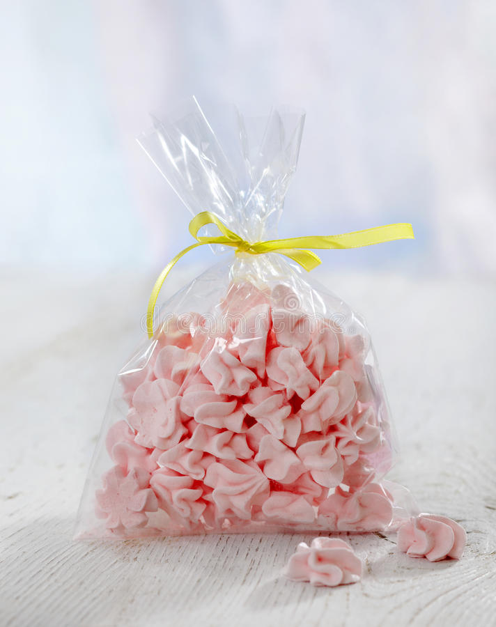 Pink meringue cookies. On white wooden table royalty free stock images