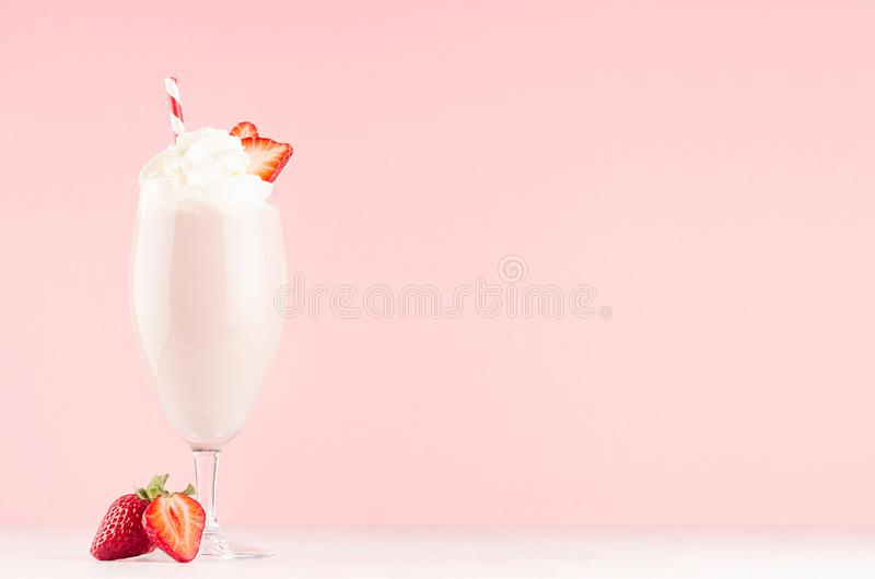 Pink milkshake with strawberry, sweet whipped cream, straw in modern stylish pink interior on white wooden table, copy space. royalty free stock photography